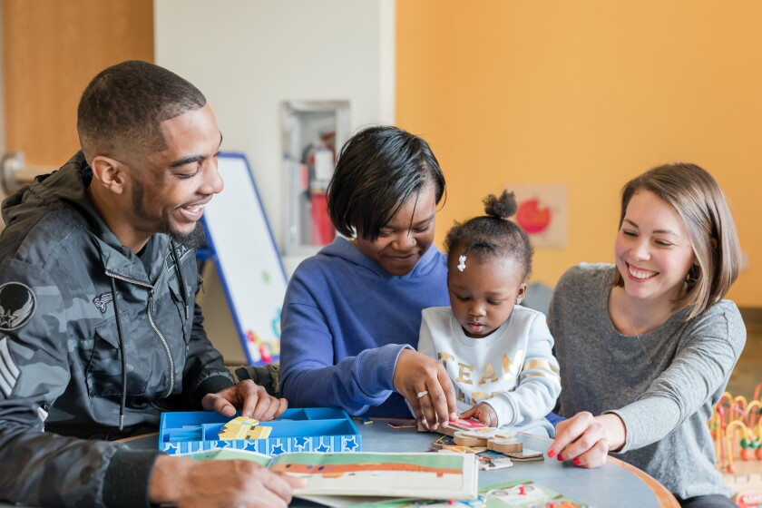 Photo of a Nurse-Family Partnership nurse visiting with a couple and their young daughter.